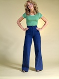 1970s Young Woman with Long Curly Hair Standing Hands on Hips in Bell Bottom Denim Blue Jeans Photographic Print