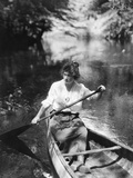 1920s Woman with Upswept Hair Paddling Wooden Canoe in Stream Photographic Print