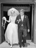 1960s Couple Bride and Groom Arm in Arm Leaving Church under Shower of Rice Photographic Print