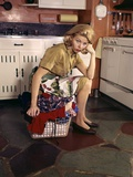 1960s Weary Dejected Woman Housewife Homemaker Sitting on Full Laundry Basket in Kitchen Photographic Print