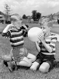1950s Two Young Boys One Blowing Up Balloon One with Fingers in Ears Afraid of Explosion Photographic Print