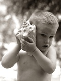 1960s Boy Toddler Holding Seashell to Ear Listening to Ocean Sounds Summer Beach Photographic Print