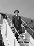 1960s Businessman Deplaning from Airplane Wearing Hat and Carrying Overcoat and Briefcase Photographic Print