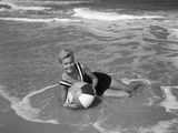 1960s Woman in Bathing Suit Lying in the Surf Holding a Beach Ball Outdoor Photographic Print