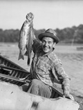 1940s-1950s Happy Man Fishing from a Rowboat Holding Up Fish Just Caught with Pride Photographic Print