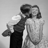 1950s-1960s Boy in Vest and Bow Tie Holding Valentine Candy Kissing Cheek of Girl Making a Face Fotografiskt tryck