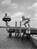 1940s-1950s Two Boys Wearing Inflatable Inner Tubes About to Jump in Lake Off Pier Photographie