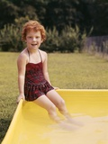 1960s Red Haired Little Girl in Plaid Bathing Suit Sitting on Yellow Plastic Backyard Swimming Pool Photographic Print
