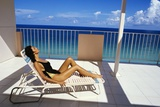 1990s Woman Wearing Black and Gold Bathing Suit Sunbathing on Patio in Deck Chair Photographic Print