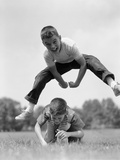 1960s Retro Boys Playing Leap Frog Outside Sky Grass Jump Jumping Crouching Photographie
