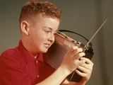 1960s Young Red Hair Pre-Teen Boy Listening to Portable Transistor Radio Held Up to Ear Photographic Print