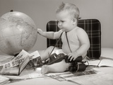 1960s Baby Seated Looking at Globe with Camera Binoculars Suitcase and Travel Brochures Photographic Print