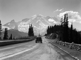 1930s Sedan Automobile Driving High Mountain Road Towards Snow Capped Mount Rainier Fotografisk trykk