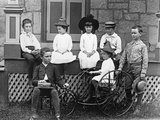 1890s-1900s Seven Children Sitting on and around Porch One Girl on Old Fashioned Tricycle Fotografiskt tryck