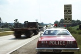 1970s Police Car with Radar Gun Checking for Speeders in 55 Mph Speed Zone Photographic Print