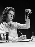 1940s Student Nurse Holding Up Test Tube While Taking Notes in Science Class Fotografisk tryk