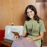 1970s Young Woman Teenager Using a Singer Sewing Machine Looking at Camera Photographic Print