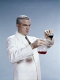 1960s Man Wearing Lab Coat Pouring Liquid from Small Erlenmeyer Flask into a Larger Flask Photographic Print