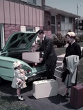 1950s Family Mother Father Daughter in Front of Suburban House Packing Luggage in Car for Vacation Photographic Print