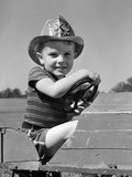 1940s Boy Playing Fireman in Toy Fire Truck Wearing Fireman's Safety Hat Holding Steering Wheel Photographic Print