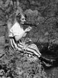 1920s Young Woman in Striped Skirt Sitting on Stream Bank in Woods Braiding Garland of Wild Flowers Photographic Print