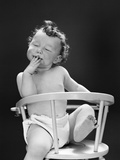 1940s-1950s Baby Sitting Backwards in High Chair with One Leg in Air Eyes Closed and Hand on Mouth Photographic Print