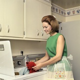 1970s Woman Housewife Homemaker Wearing Apron Loading Laundry into Washing Machine Photographic Print