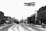 Biplane over a Small Town Photographic Print by J.H. Cave