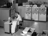 1960s Man Programming Large Mainframe Computer Surrounded by Data Tape Drives Indoor Photographic Print by H. Armstrong Roberts