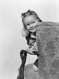 1940s Little Girl Holding Doll Peeking around Side of Chair Photographic Print