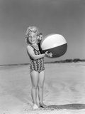 1950s Smiling Little Girl Standing on Beach Holding Beach Ball Photographic Print