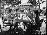 1930s Three Women and One Man Sitting at Tropical Pool Side Table Talking Together Reproduction photographique