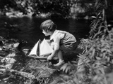 1920s Boy Putting Toy Sailboat into Stream Photographic Print
