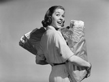 1950s Smiling Woman Carrying Grocery Bags Both Hands over Her Shoulder Photographic Print