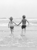 1960s Two Children Holding Hands Running into Water Photographic Print