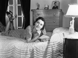 1940s Fully Dressed Smiling Woman Laying on Her Bed with Her Legs Up Reading a Letter Photographic Print