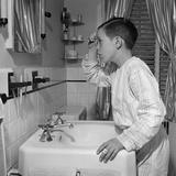 1950s Boy Combing Hair Looking in Bathroom Sink Mirror Photographie par E. Hibbs