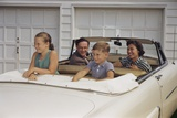 Family Sitting in Car Outside Garage Photographic Print by William P. Gottlieb