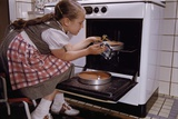 Girl Wearing Apron Removing Cakes from Oven Photographic Print by William P. Gottlieb