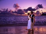 Dressed Up Couple Embracing on the Beach at Sunset Reproduction photographique