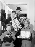 1960s Family Standing in Doorway Wearing Winter Coats and Holding Christmas Presents Photographic Print