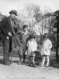 1920s Group of Three Children Watching Organ Grinder's Monkey in Costume Standing on Hind Legs Photographic Print