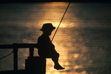 Silhouette of Child Fishing Off a Dock at Sunset Photographic Print