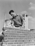 1940s Man Working with Level on Brick Wall Chimney Construction Photographic Print