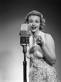 1950s Portrait of Woman Singing into a Microphone Photographic Print