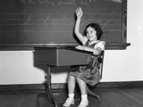 1930s-1940s Smiling Girl Sitting at Desk Raising Her Hand Photographic Print