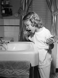 1950s Little Blond Girl in Pajamas Standing at Bathroom Sink Brushing Her Teeth Stampa fotografica di E. Hibbs