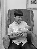 1960s Pre-Teen Boy Sitting in Armchair Holding Infant Newborn Baby Sibling Photographic Print