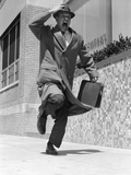 1950s-1960s Frantic Man Running Down Street Holding Hat on with Hand Carrying Briefcase Reproduction photographique