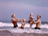 1970s Family Laughing Hand Holding Jumping in Ocean Surf at Beach Photographic Print
